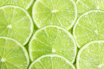 Fresh sliced ripe limes as background, top view