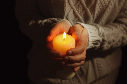 Young person holding burning candle in darkness, closeup