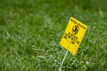 Yellow Pesticide Application Warning On Green Lawn