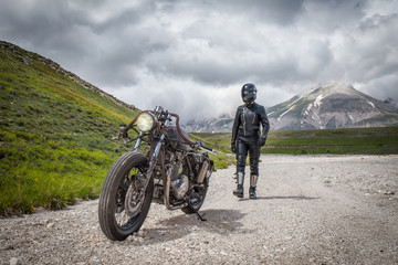 Biker with black leather clothes, walking near his custom rat motorcycle in a desolated mountain land. Post apocalyptic concept