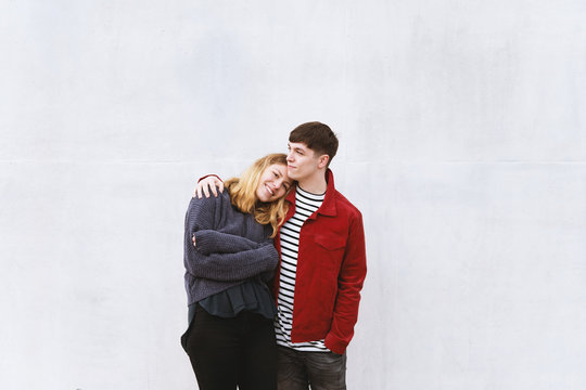 young affectionate couple standing in front of concrete cement wall with copy space