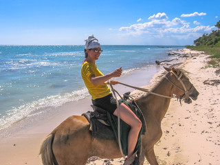Young tourist on horseback along the coast of Parque Nacional Del Este, East National Park, Dominican Republic. Horse riding is an activity widely practiced in Bayahibe, popular tourist village.