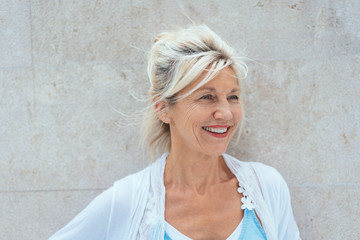 Blonde mature smiling woman against bright wall