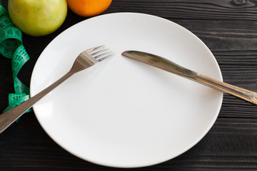 Hand hold fork and knife with plate on wood. Female hands with cutlery and empty plate on wooden background
