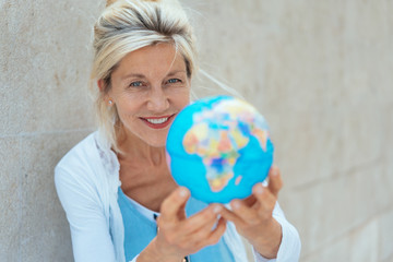 Cheerful senior woman holding globe