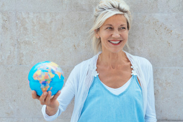 Smiling older blond woman holding a globe