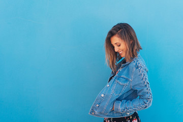 Smiling, pretty, shy girl with blue copy space