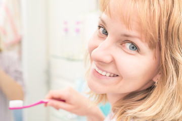 Pretty young female looking at camera while brushing teeth in bathroom. Happy woman cleaning her oral cavity caring about dental health.