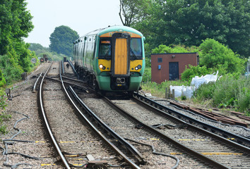 An electric train approaching  a road crossing in the UK