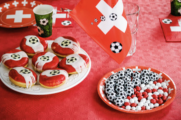 Doughnuts with red glaze and football decoration on red table cloth background. Chocolate candy football shaped on plate. Football toothpicks and flags with swiss cross. Football party in Switzerland.