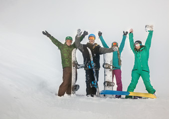 Four happy friends snowboarders in mountains