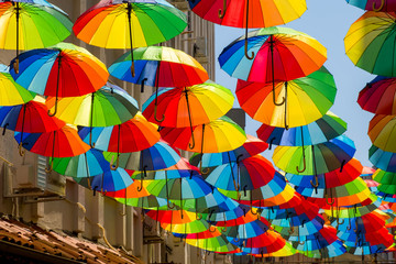 Multicolored, rainbow, umbrellas hung over the street.