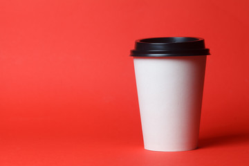 Paper coffee container with black lid on red background. Takeaway drink container. Template of drink cup for your design. Can put text, image, and logo.