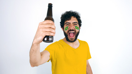 Sport fan holding a beer screaming for the triumph of his team. Man with the flag of Brazil makeup on his face and yellow t-shirt.