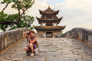 Tourist girl taking pictures on ancient Chinese bridge