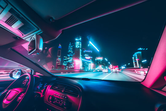 Car speed drive on the road in night city. Retro wave neon noir lights color toning