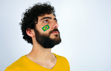 Sport fan head high and feeling proud when listening to the anthem of his country. Man with the flag of Brazil makeup on his face and white t-shirt.
