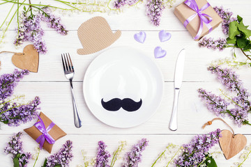 Father's Day table setting with cutlery and spring flowers on white wooden table.