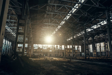 Abandoned industrial creepy warehouse inside old dark grunge factory building in sunlight