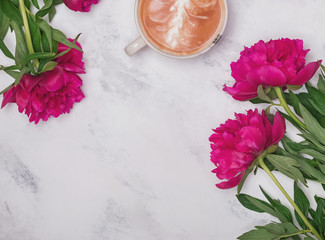 Beautiful pink peonies and coffee on the marble background