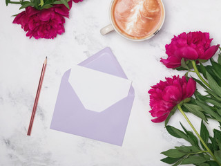 Coffee, peonies and envelope on the marble background