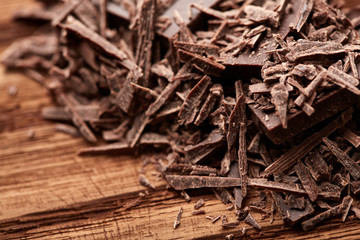 crumbs of black chocolate on a wooden background
