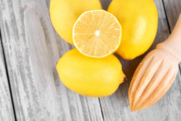 Freshly squeezed lemon juice. A glass of squeezed lemon juice and lemons around. Vitamins. Citrus fruits. Yellow.