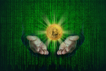 Bitcoin golden metallic coin on hands of business with binary code of matrix effect background.