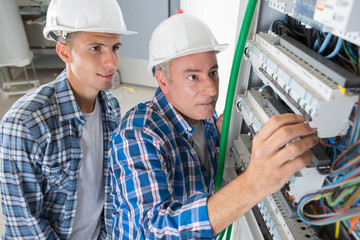 electrician engineer workers in front of fuse switch board