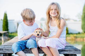 Adorable boy and girl sitting on wooden bridge and playing with their Golden Cocker Spaniel puppy dog near the lake at summer day. Kids and animals friendship concept.
