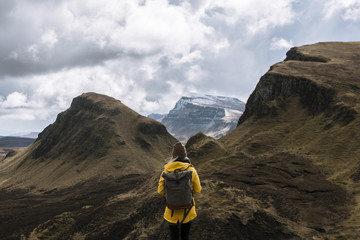 Happy Girl with backpack and yellow jacket enjoying a mountain view in Quiraing on the Isle of Skye, Scotland