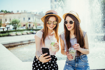 Photo of pleased two mixed race women get good news on mobile phone, recieve email or make selfie with smart phone, drink fresh cocktails outdoors.