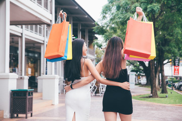 Happy young women with shopping bags enjoying in shopping on holiday.Consumerism and lifestyle concept.Black Friday sale