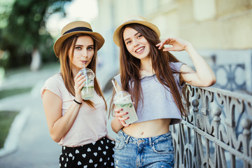 Two young women in summer clothes talk and drink cold cocktails, pretty friends. Nice girlfriends walk around the city and drink lemonade. close up portrait