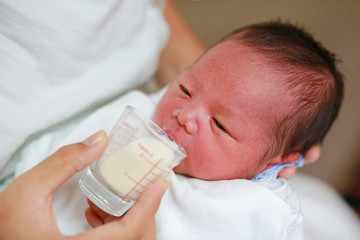 Newborn Baby drinking milk from glass cup.