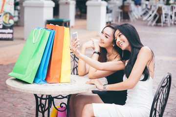 Two happy young female friends take selfie picture by smart phone,