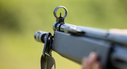 Shotgun in man' s hand. Front side of weapon with close up view on blurred nature background.
