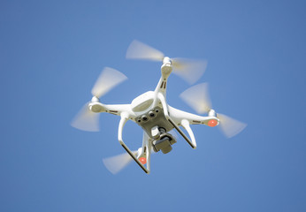 White drone with digital camera, filming from above. Clear blue sky background.