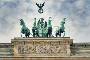 Quadriga on the neoclassical monument Brandenburg Gate with dramatic cloudy sky background, Berlin, Germany