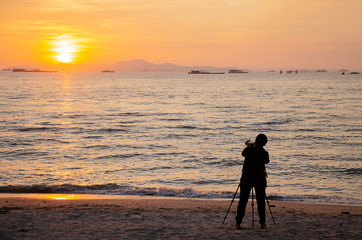 Silhouette of professional photographer shooting sunset with good lens, camera and tripod at the beach on sunny hot day in summer with calm clear sea and sky