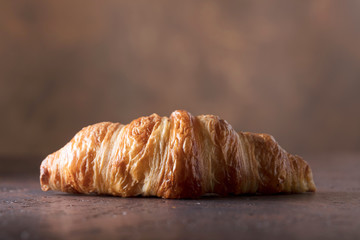Fresh and tasty croissant  on old copper background.
