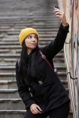 Giovane  con cuffia gialla si fa un selfie con il suo cellulare - sfondo scalinata