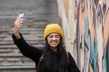 Giovane ragazza felice con cuffia gialla si fa un selfie con il suo cellulare - sfondo scalinata