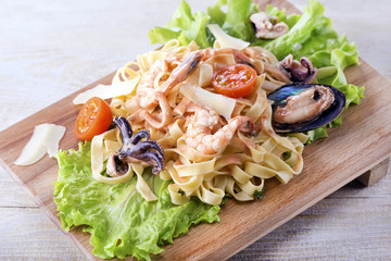 Fettuccine pasta with shrimp, tomatoes and herbs on wooden board.Italian cuisine. Top view