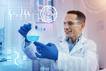 Excited scientist. Positive enthusiastic clever scientist feeling impressed and smiling while sitting with a glass bottle in his hands