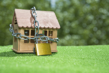 House closed on a lock with a chain. against the background of grass and greens. concept of protection