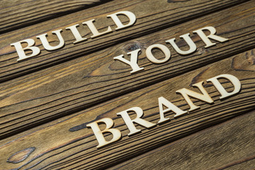 build your brand text is composed of letters on a wooden background. The concept of business, motivation.