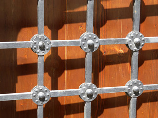 Metal lattice on the background of old wooden doors, medieval facade. Vintage lattice and wooden gates