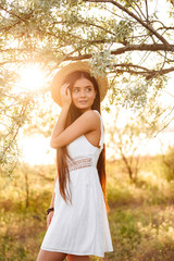 Photo of beautiful young woman with long dark hair wearing straw hat and white dress looking away, while standing under tree in nature during bright sunny day