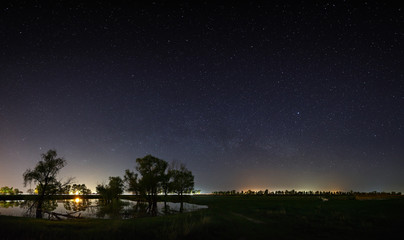 Space with the stars of the Milky Way in the night sky. The landscape with the river and trees is photographed on a long exposure.